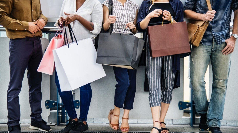Menschen, die am Black Friday Angebote zum Shoppen genutzt haben, stehen mit Einkaufstueten in einer Reihe